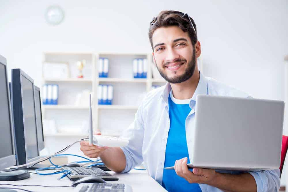 Young IT professional offering Managed Services holding a laptop and smiling.